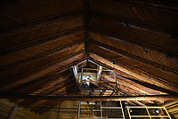 Tyler Merrill of the Rocky Mountain Youth Corp. works to dismantle the latilla ceiling during preservation efforts of the Crandall Studio at the Jenny Lake Visitor Center complex. The ceiling is unique to the building, which was built in 1925 by Grand Teton National Park photographer Harrison Crandall. The structure was moved from its original site north of Jenny Lake to its current location and serves as the Jenny Lake Visitor Center.