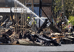 © Licensed to London News Pictures. 04/05/2021. London, UK.  Fire fighters continue to damp down the remains of two boatyards on Platt's Eyot, an island on The River Thames in south west London after yesterday's blaze. It is being reported that a Dunkirk Little Ship The Lady Gay was damaged in the fire as it was on a slipway at the yard.  Photo credit: Peter Macdiarmid/LNP