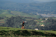 Mountain biker biking in rural green hills in spring, Briones Regional Park, Conta Costa County, California