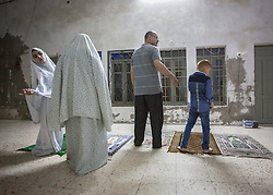 "© Licensed to London News Pictures. 15/07/2014. Gaza.      The Al Tourek family  prepare to prayer following her family  Iftar feast  in Gaza city. <br /> <br /> After a short ceasefire broke down Hamas and Israel have now resumed their current campaign.   ""Every night when we sit to eat we can hear the explosions.  This should be a happy time for use but we are just living in fear.""  Commented Bassen Al Tourek, the father of the family.   Photo credit : Alison Baskerville/LNP"
