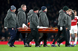 Arsenal's Hector Bellerin is carried off on a stretcher by medics during the match