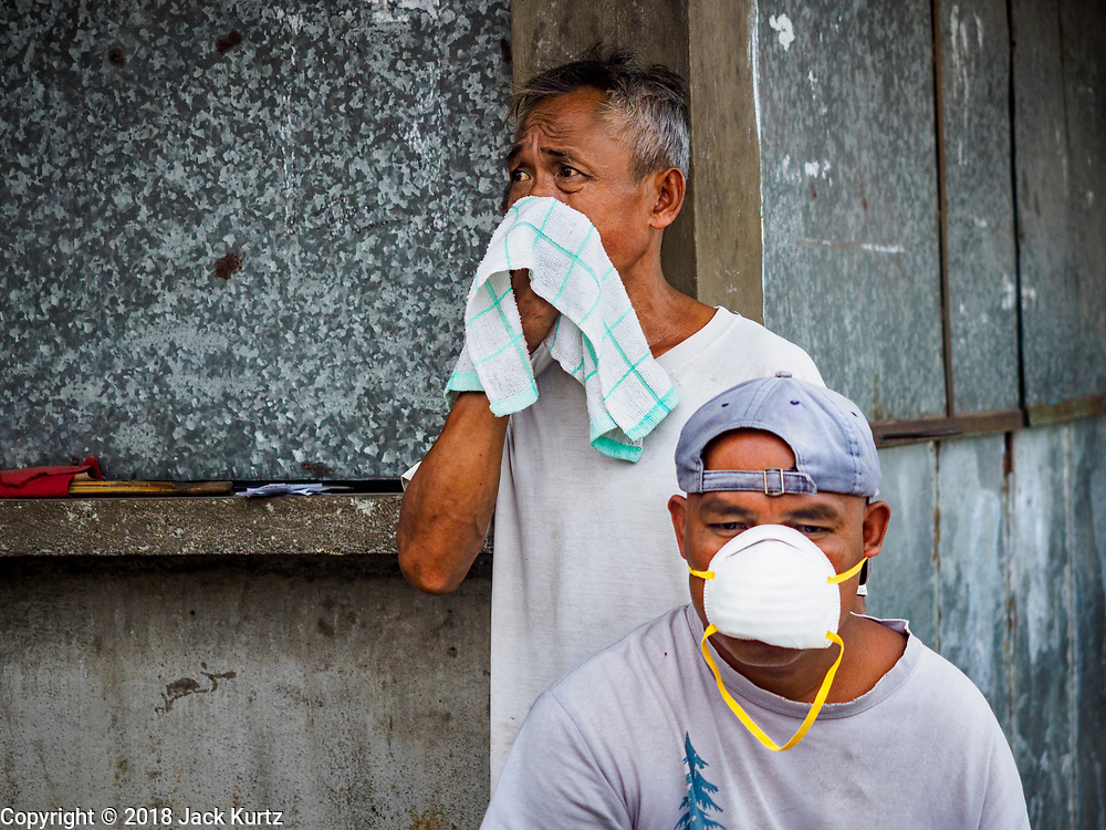 """22 JANUARY 2018 - GUINOBATAN, ALBAY, PHILIPPINES: Men in Guinobatan wear face masks because of an ash fall caused by the eruption of Mayon volcano. Several communities in Guinobatan were hit ash falls from the eruptions of the Mayon volcano and many people wore face masks to protect themselves from the ash. There were a series of eruptions on the Mayon volcano near Legazpi Monday. The eruptions started Sunday night and continued through the day. At about midday the volcano sent a plume of ash and smoke towering over Camalig, the largest municipality near the volcano. The Philippine Institute of Volcanology and Seismology (PHIVOLCS) extended the six kilometer danger zone to eight kilometers and raised the alert level from three to four. This is the first time the alert level has been at four since 2009. A level four alert means a """"Hazardous Eruption is Imminent"""" and there is """"intense unrest"""" in the volcano. The Mayon volcano is the most active volcano in the Philippines. Sunday and Monday's eruptions caused ash falls in several communities but there were no known injuries.    PHOTO BY JACK KURTZ"""