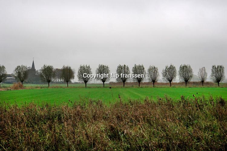 Nederland, Persingen, 2-12-2020  Landelijk gebied rond dit dorpje, gehucht, in de Ooijpolder. De toren van het karakteristieke kerkje, kerktoren, is zichtbaar boven de bomen Er is aangegeven dat dit een stiltegebied is. De Ooijpolder is onderdeel van de wandelroute, pelgrimsroute, walk of wisdom door het rijk van Nijmegen. Foto: ANP/ Hollandse Hoogte/ Flip Franssen