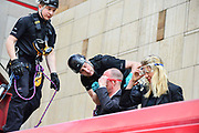 Police officers fit two climate change protesters with goggles as they  begin to remove the pair  who glued herself to the roof of a Docklands Light Railway carriage on April 17, 2019 in  London,England, United Kingdom.This is the third day of a coordinated protest by the Extinction Rebellion group who are demanding the government decisive action from the UK Government on climate change.