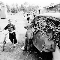 Romas children in a makeshift camp in Kraljevo...Romas children do not receive the same attention as the other IDPs children: they do not go to school and they do not receive any assistance as far as health is concerned. Because the families did not have documents, they could not be registered officially as IDPs...During the summer1999, over 245,000 Serbs and Roms fled to Serbia and Montenegro from or within Kosovo in fear of reprisals from the majority Albanian population, after NATO air strikes had forced the withdrawal of Yugoslav. In 2003, less than 2% of them had returned and a large number of these internally displaced persons (IDPs) were still living in camps in very difficult conditions..In addition, around 5,000 IDPs, mainly of Roma ethnicity, are living in unrecognized collective centres, makeshift huts, corrugated metal containers and other substandard shelters. .This work was meant to look at how the life of children and young adults is affected by the fact that they are IDPs. I asked myself more specifically what would be different for these children/young adults from the 'normal' people of their age as far as education, health, social life, family, 'love' life and leisure are concerned. ...Enfants roms dans un camp improvisé de Kraljevo. ..Les enfants roms ne vont pas à l'école et ne reçoivent aucune assistance médicale. Faute de papiers d'identité, ils n'ont pu être officiellement enregistrés en tant qu'IDP...Pendant l'été 1999, plus de 245 000 serbes et roms ont fuit le Kosovo pour chercher refuge en Serbie ou au Montenegro, par peur de représailles de la part de la majorité de la population albanaise après que les forces de l'OTAN aient forcé l'armée yougoslave à se retirer. En 2003, moins de 2% d'entre eux étaient rentrés chez eux et le plus grand nombre de ces 'déplacés' (IDPs) vivaient encore dans des centres d'accueil dans des conditions très difficiles..Environ 5 000 IDPs, la plupart romas, vivent dans des centres non reconnus faits de containe