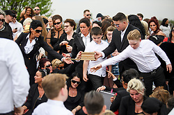 © Licensed to London News Pictures. 21/04/2018. London, UK. Mourners shown dirt in the the grave at the burial of traveller 'Queenie, Elizabeth Doherty at Kensal Green Cemetery in west London, following a funeral service in Cobham, Surrey. Elizabeth Doherty, whose son Paddy Doherty is known for appearing on My Big Fat Gypsy Wedding and winning Celebrity Big Brother 8, died of a heart attack earlier this month. Paddy Doherty claimed his mother has died of a 'broken heart' following the death of her husband almost a year ago. Photo credit: Ben Cawthra/LNP