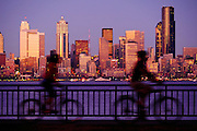 Twilight view of downtown Seattle, Washington across Elliot Bay from West Seattle with two cyclists