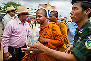 16 JUNE 2014 - POIPET, CAMBODIA: Cambodian Buddhist monks return to Poipet, Cambodia from Thailand. More than 150,000 Cambodian migrant workers and their families have left Thailand since June 12. The exodus started when rumors circulated in the Cambodian migrant community that the Thai junta was going to crack down on undocumented workers. About 40,000 Cambodians were expected to return to Cambodia today. The mass exodus has stressed resources on both sides of the Thai/Cambodian border. The Cambodian town of Poipet has been over run with returning migrants. On the Thai side, in Aranyaprathet, the bus and train station has been flooded with Cambodians taking all of their possessions back to Cambodia.  PHOTO BY JACK KURTZ