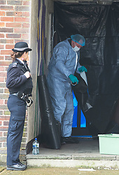 © Licensed to London News Pictures 06/02/2021.        Croydon, UK. A forensics officer on scene this morning hanging plastic sheeting around the entrance door to the flats with gaffer tape. A man has been killed and ten others have been stabbed with two in a life threatening condition in hospital after a night of knife violence in Croydon, South London. Police have put a large cordon in place at the murder scene in Wisbeach Road. Photo credit:Grant Falvey/LNP