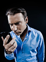 one caucasian man angry looking at telephone videophone smartphone  portrait isolated studio on black background