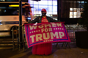 """New York, NY - 3 November 2020. New York City anticipates presidential election results as polls in some states close. A woman on Fifth Avenue near Trump Tower wears a Keep American Great hat, an All Lives Matter mask, and displays a banner that reads """"Women For Trump."""""""