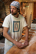 Jamestown, RI - 7 May 2007. Andrea Colognese, baker and co-owner of The Village Hearth Bakery and Cafe, shaping bread.