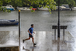 Licensed to London News Pictures. 17/05/2021. London, UK. A runner gets caught in torrential rain in Richmond, south west London as the miserable May weather drags on. Today Government's roadmap out of lockdown continues with pubs, restaurants, cafes and bars able to serve customers inside. However Downing Street has warned that due to the Indian variant, local lockdowns could be quickly reintroduced in high risk areas. Photo credit: Alex Lentati/LNP