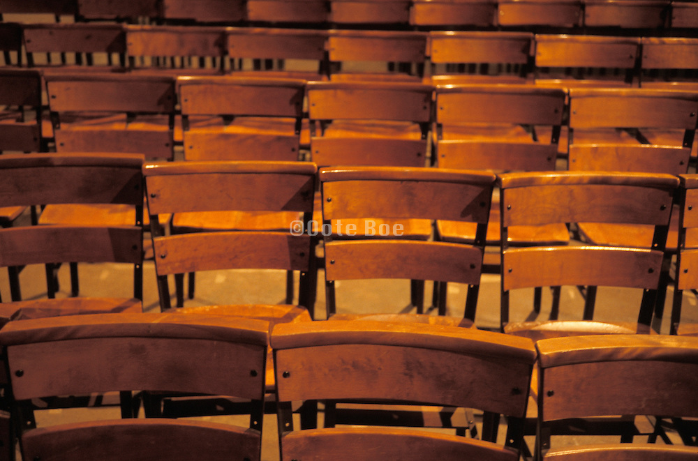 empty rows of wooden chairs