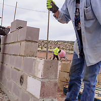 John Rosin and other race association members construct lay blocks and mix cement at the Uranium Capital Speedway in Milan Saturday.