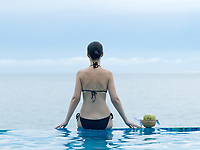 woman siiting on a the edge of a swimming pool looking at the sea