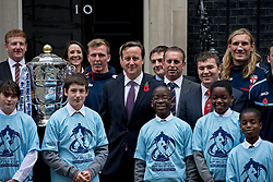 © London News Pictures. 31/10/2012. London, UK.  British Prime Minister DAVID CAMERON posing with members of the England and Wales Rugby League squad and children from Brixton Bulls and Croydon Huricane Rugby Clubs holding the Rugby League World Cup outside number 10 Downing Street on October 31, 2012 to promote the Rugby League World Cup being played in Britain this winter.  Photo credit: Ben Cawthra/LNP