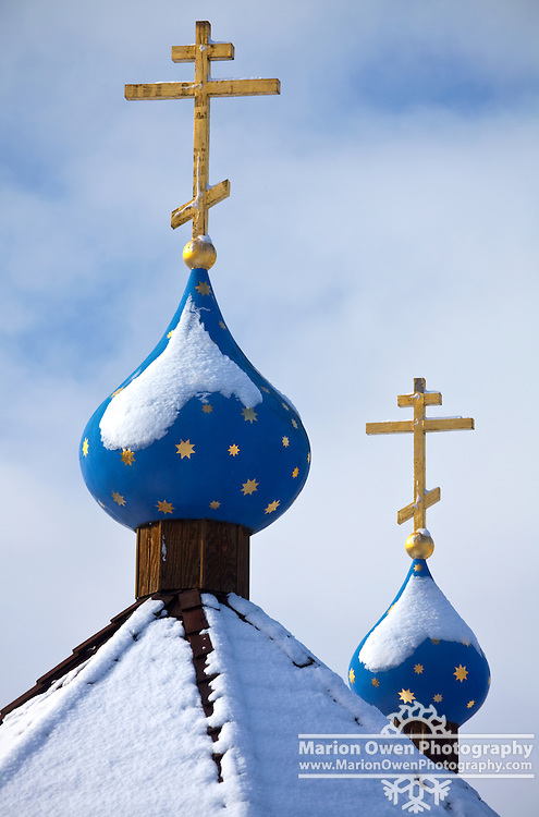 Gold Russian Orthodox crosses on top of blue and gold star cupolas at the Saint Herman Theological Seminary in Kodiak, Alaska.