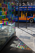 A tour bus drives past coloured light from a corner cafe reflected on the pavement inn Fleet Street in the City of London, the capitals financial district aka the Square Mile, on 22nd August 2019, in London, England.