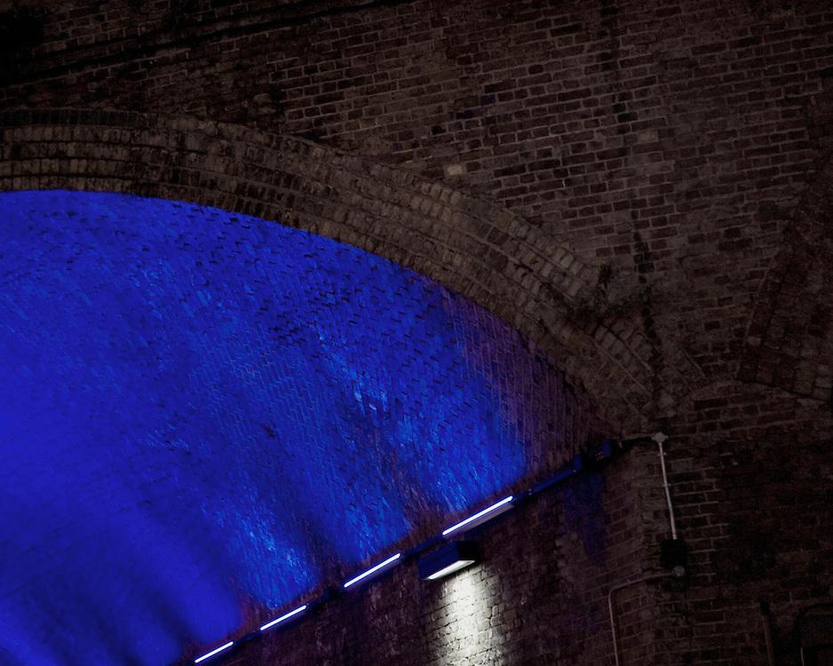 Blue neon light under a bridge