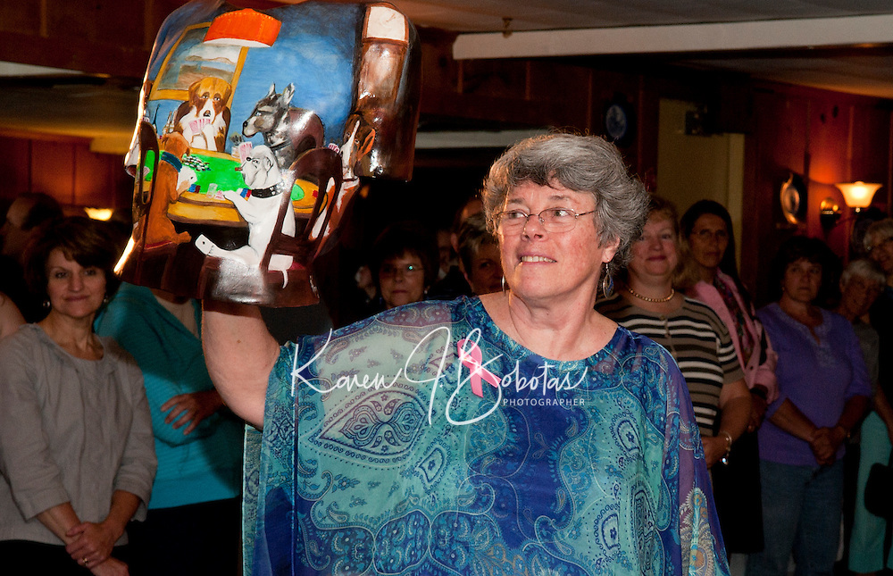 """Shirley Stokes presented the """"Dogs Playing Cards"""" by one of the male models to the crowd gathered at Hart's Turkey Farm for the Save Our Treasured Chests live auction on Wednesday evening.   (Karen Bobotas/for the Laconia Daily Sun)"""