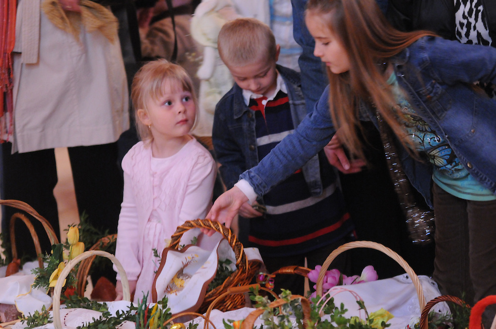 Attendees of a traditional Holy Saturday Blessing of the Easter Baskets look for their own feasts placed before the alter for blessing by Francis Cardinal George at Our Lady, Mother of the Church Polish Mission in Willow Springs.