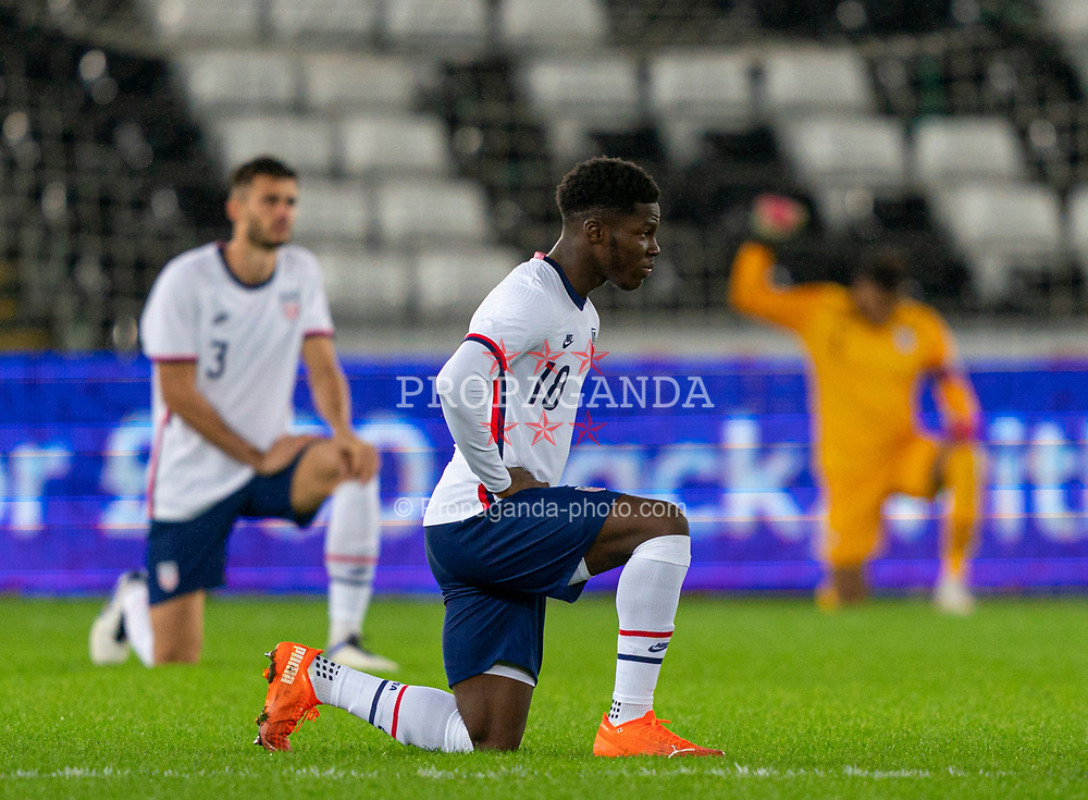SWANSEA, WALES - Thursday, November 12, 2020: USA's Yunus Musah kneels down (takes a knee) in support of the Black Lives Matter movement before an International Friendly match between Wales and the USA at the Liberty Stadium. (Pic by David Rawcliffe/Propaganda)