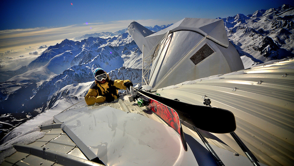 """Nicholas Marchionini climbing over the observatory domes to access the north face of Picdu Midi de Bigorre for the first descent and opening of """"Por Favor"""" , the last un-skied line of this famous peak. Pyrenees, France."""