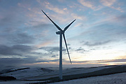 Wind turbines harnessing the natural green energy in the Scottish Borders on 28th December 2020 in Galashiels, Scotland, United Kingdom. The wind farm, Longpark Wind Farm, is long established and part of the renewable energy production in Scotland. The farm sits in the hills above the village Stow, near Galashields in the Scottish Borders. In between the wind turbines sheep grass in the fields lightly covered by snow.