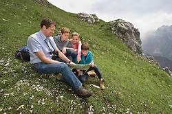 Father and kids looking at hiking map in Alps