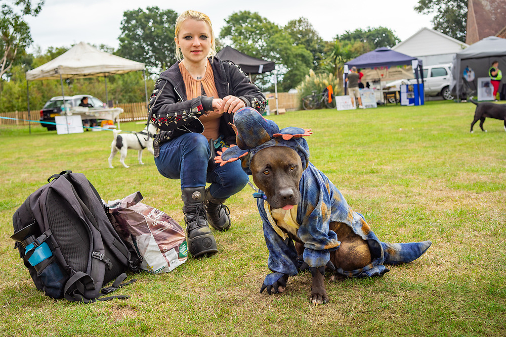 Young female dog owner in Goth clothing with her dog in Climping, West Sussex, England, UK