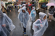 London, UK. Sunday 23rd August 2015. Heavy summer rain showers in the West End. People brave the wet weather armed with umbrellas and waterproof clothing. Tourists in plastic macs on Gerrard Street in Chinatown.