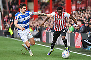 Brentford Midfielder Moses Odubajo (2) and Queens Park Rangers Midfielder Pawel Wszolek (23) battle for the ball during the EFL Sky Bet Championship match between Brentford and Queens Park Rangers at Griffin Park, London, England on 2 March 2019.
