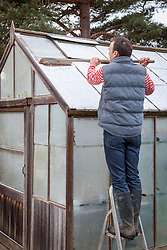Brushing snow of a greenhouse roof