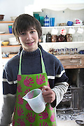 Model released image young teenage boy wearing an apron in family kitchen, UK