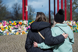 © Licensed to London News Pictures. 13/03/2021. LONDON, UK.  London, UK.  13 March 2021.  A couple views floral tributes at the bandstand on Clapham Common to remember Sarah Everard.  Wayne Couzens, 48, a serving Met Police officer, has been charged with her kidnap and murder after she walked home in south London.  The 33-year-old's body was found in woodland in Kent more than a week after she was last spotted on 3 March.  Photo credit: Stephen Chung/LNP