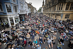 © Licensed to London News Pictures. 09/06/2020. Oxford, UK. Campaigners sit in the road outside Oriel College at Oxford University, where they are calling for the removal of a statue of controversial imperialist Cecil Rhodes. Black Lives Matter protesters recently pulled down a statue of slave trader Edward Colston in Bristol town centre, following the death of George Floyd in the USA . Photo credit: Peter Macdiarmid/LNP