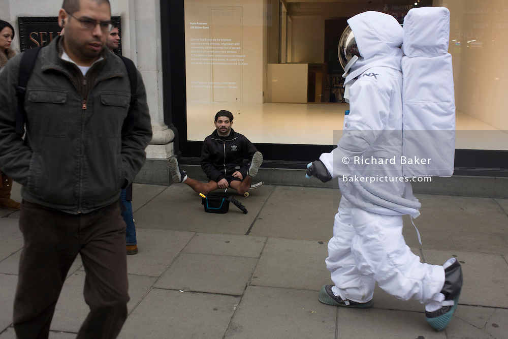 London 8/1/13: Passing a disabled beggar, a man dressed as a NASA moon walking astronaut walks along Oxford Street outside the Selfridges department store in central London - part of a PR promo for deodorant brand Lynx who have launched a competition, with the first prize a once-in-a-lifetime chance to blast into orbit. The 22 winners, which will include one Brit, will experience Earth from outer space on the Lynx SXC (Space Expedition Corporation) space shuttle. Shoppers and passers-by seem oblivious to this symbol of 20th century American technology, now reduced to a PR stunt for the Lynx aftershave brand hosted by Selfridges. Selfridges, also known as Selfridges & Co, is a chain of high end department stores in the United Kingdom. It was founded by Harry Gordon Selfridge. The flagship store in London's Oxford Street is the second largest shop in the UK (after Harrods) and opened 15 March 1909.
