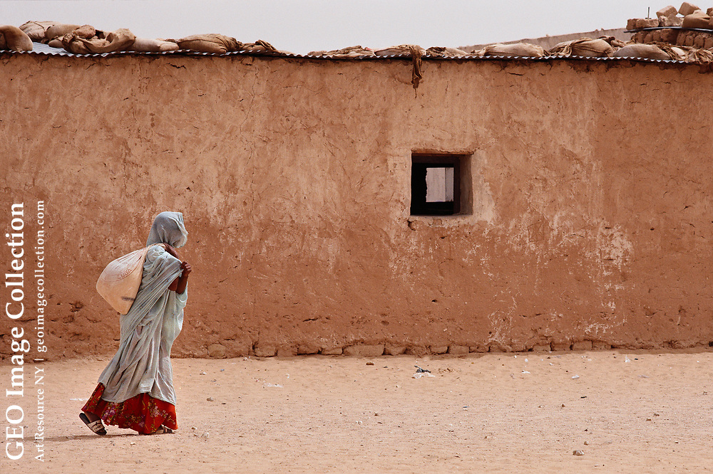 One of some 170,000 refugees from the dispute territory of Western Sahara leaves a Red Cross food distribution center at with a sack of powdered milk from Cuba.  The conflict over Western Sahara has smoldered for more than 40 years, leaving the Sahrawis people exiled in several campus around Tindouf, Algeria.