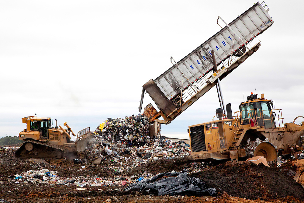 Crane lifts and dumps load of municipal solid waste transfer truck in open cell of sanitary landfill