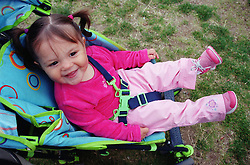 Portrait of girl with hair in bunches sitting in pushchair smiling,