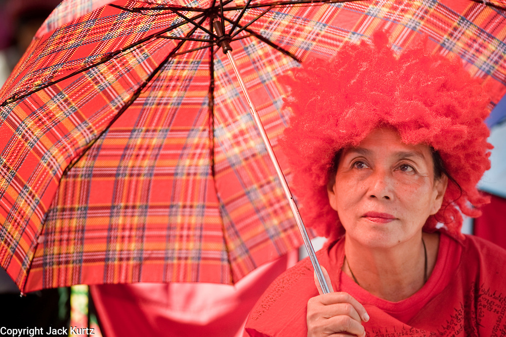 """09 MAY 2010 - BANGKOK, THAILAND: A Red Shirt woman in a red outfit and a red wig sits under a red umbrella at the Red Shirt rally in Bangkok Sunday. The Red Shirt leaders said Sunday they still conditionally supported the Prime Minister's """"Road Map to Reconciliation"""" but that their opponents the Yellow Shirts needed to sign on to make the five point """"Road Map"""" viable. About 5,000 people mostly from northeast Thailand, joined the Red Shirts in Ratchaprasong over the weekend. Members of the United Front of Democracy Against Dictatorship (UDD), also known as the """"Red Shirts"""" and their supporters have occupied Ratchaprasong intersection, the site of Bangkok's fanciest shopping malls and several 5 star hotels, since April 4. The Red Shirts are demanding the resignation of current Thai Prime Minister Abhisit Vejjajiva and his government. The protest is a continuation of protests the Red Shirts have been holding across Thailand. They support former Prime Minister Thaksin Shinawatra, who was deposed in a coup in 2006 and went into exile rather than go to prison after being convicted on corruption charges. Thaksin is still enormously popular in rural Thailand.   PHOTO BY JACK KURTZ"""