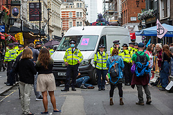 © Licensed to London News Pictures. 23/08/2021. LONDON, UK.  A police cordon surrounds climate activists from Extinction Rebellion under a stationary van on St Martin's Lane during a protest in Covent Garden.  The group has announced that it will stage protests in the capital for the next two weeks as they try to raise awareness of the effects of big business on climate change.  Photo credit: Stephen Chung/LNP