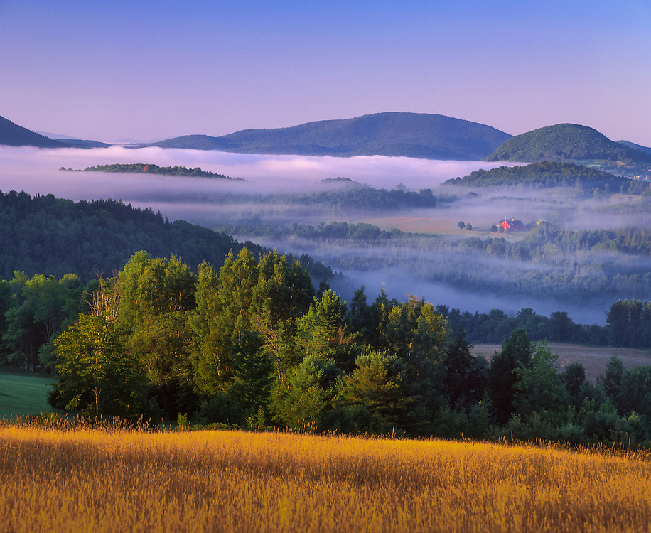 First light on hills and field with rising fog and distant farm, Peacham, VT