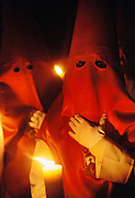 Hooded penitents in a night-time procession during Holy week in Seville, Spain. Street processions are organized in most Spanish towns each evening, from Palm Sunday to Easter Sunday. People carry statues of saints on floats or wooden platforms, and an atmosphere of mourning can seem quite oppressive to onlookers.