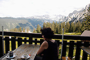 Austria, Upper Austria, Gosau, in the Dachstein Mountains. Woman at a restaurant at the mountain top Model Release available