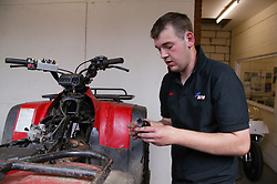 Man with Cerebral Palsy working as mechanic; repairing all terrain vehicle in workshop,