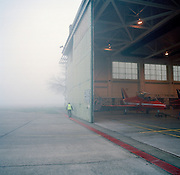 On a misty morning, a red Hawk jet aircraft belonging to the elite 'Red Arrows', Britain's prestigious Royal Air Force aerobatic team, is parked in the hangar at RAF Scampton, Lincolnshire, the home base for the squadron. The aircraft awaits attention from the engineer's night-shift who service and maintain all 11 of the famous red aerobatic jets before flying the next morning. The hangar, an original World War 2 shelter for the Lancaster bombers of 617 Dambusters squadron who attacked the damns of the German Ruhr valley on 16th May 1943 using the Bouncing Bomb. The Red Arrows use this and nearby offices administrative nerve-centre for the 90-plus displays they perform a year..