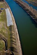 Nederland, Limburg, Gemeente Leudal, 07-03-2010; rivier de Maas, uitlaatwerk voor het retentiegebied Lateraalkanaal-West, tussen Horn en Haelen. De dijk van het kanaal parallel aan de Maas is verlaagd en bekleed met open-steenasfalt. Bij (extreem) hoogwater stroomt er verder stroomopwaarts water in het retentiebekken (via het inlaatwerk) en de extra wateropvang geeft verder stroomafwaarts een daling van de waterspiegel. .Maas river, outlet work (or vent) for the retention basin Lateral Canal West, between Horn and Haelen. The dike of the canal parallel to the Maas has been lowered and covered with open stone asphalt. With (extremely) high water the basinwill fill further upstream, and as a result further downstream the water levels will drop. .luchtfoto (toeslag), aerial photo (additional fee required);.foto/photo Siebe Swart