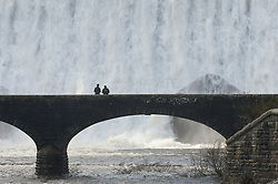 © Licensed to London News Pictures. 11/02/2019. Elan Valley, Powys, Wales, UK. Visitors watch from a bridge as water cascades over the Caban-coch dam, at Elan Valley village near Rhayader in Powys, Wales, UK after recent torrential rain in Powys has filled the complex of Elan valley dams and taken river levels to the tops of river banks in Powys, Wales, UK. Elan Valley dams supply Birmingham in the West Midlands UK with water via a gravity feed. credit: Graham M. Lawrence/LNP